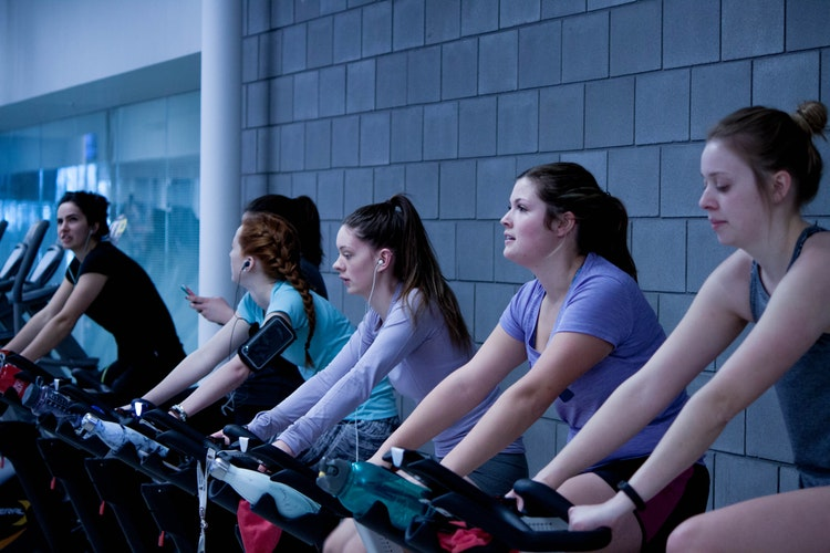 a group of ladies working out on bikes in a spinning class
