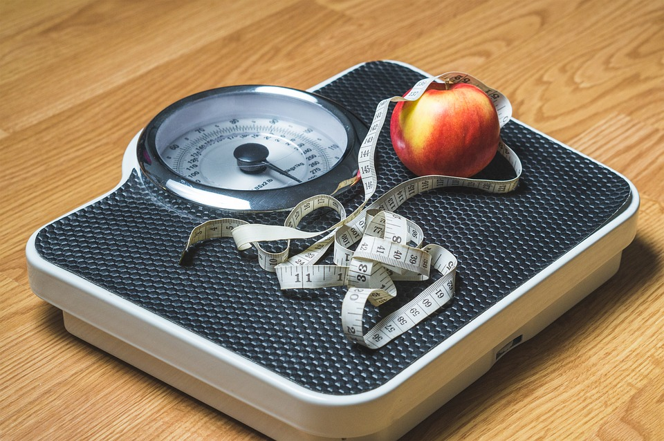 weighing scales with an apple and measuring tape on top