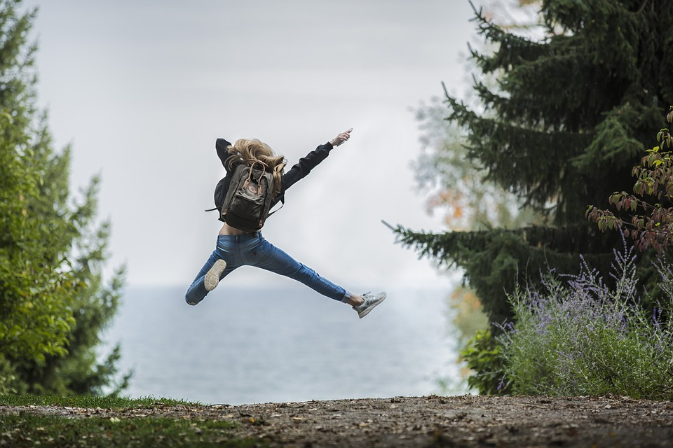 A person jumping in the air with excitement, facing a view of trees and water