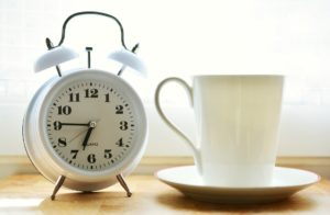 A white alarm clock and white cup and saucer on a wooden table