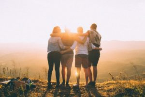 A group of four people looking outwards with arms around each other