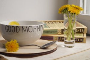A bowl, plate, spoon, a few books and a small glass of water with yellow flowers on a table