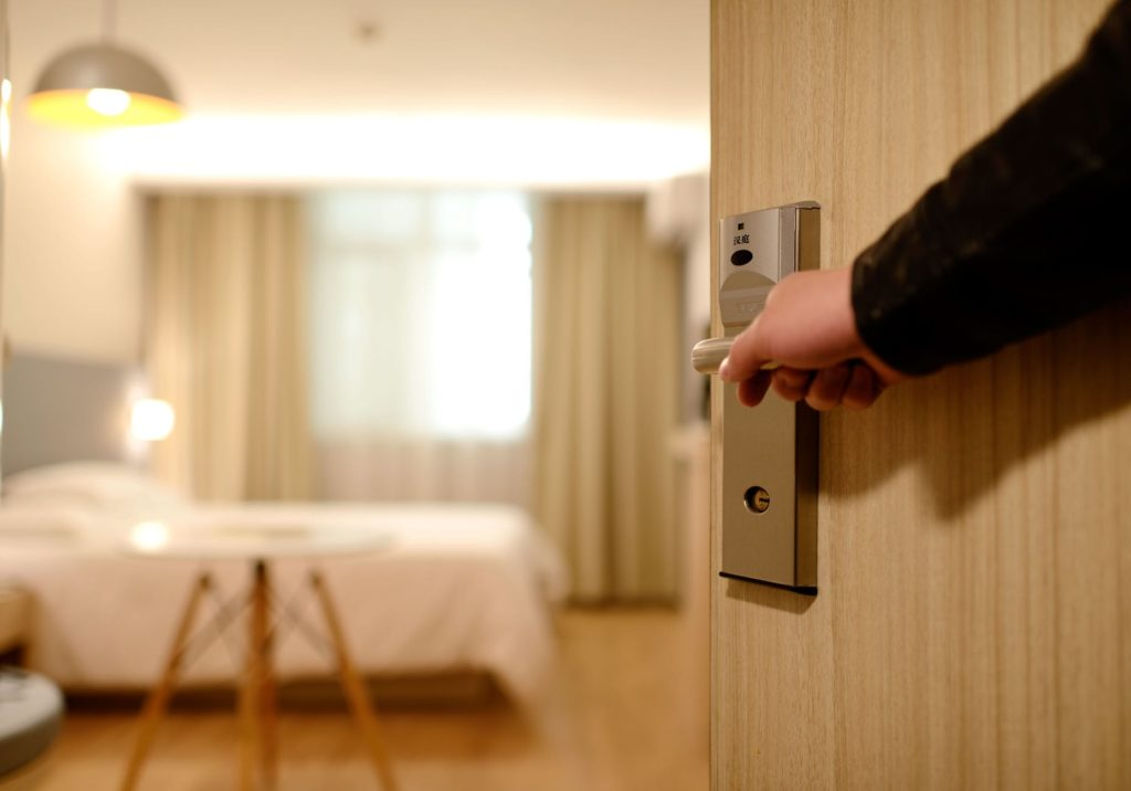 A hand opening a door into a hotel room
