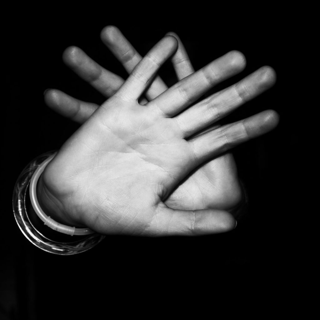 Hands being held up in front of face