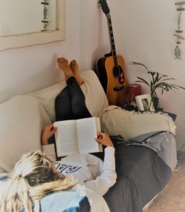 A woman laying on her back on the sofa with her legs up resting on the top of the sofa, reading a book
