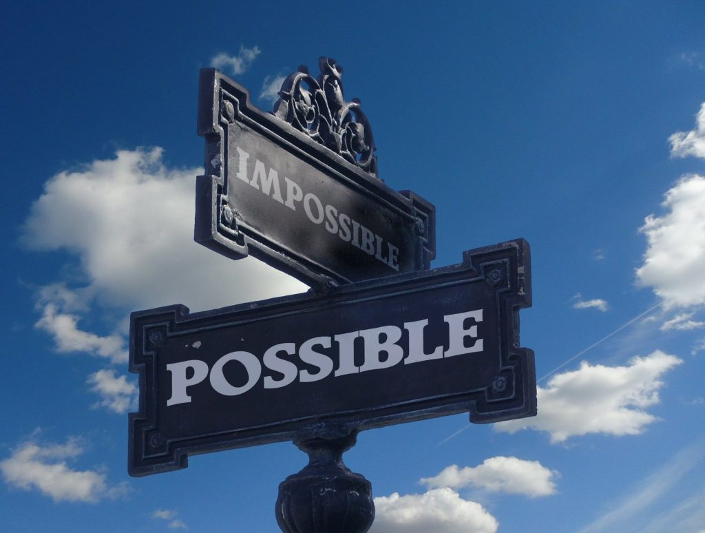 A signpost with one direction saying Impossible and the other direction saying possible