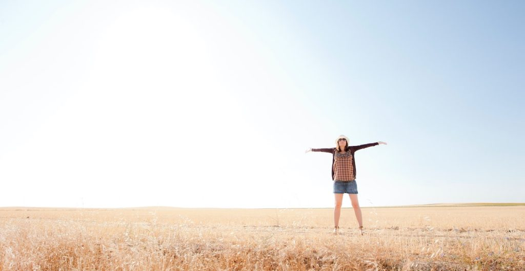Woman in a field in the power pose