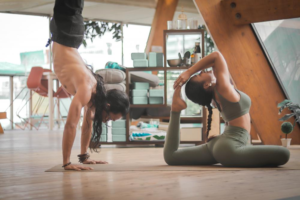 Movement snacking man handstanding and woman in yoga pose in the office