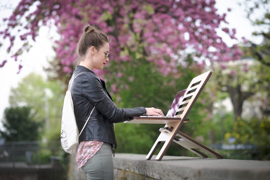 woman using a standing desk to keep active working from home