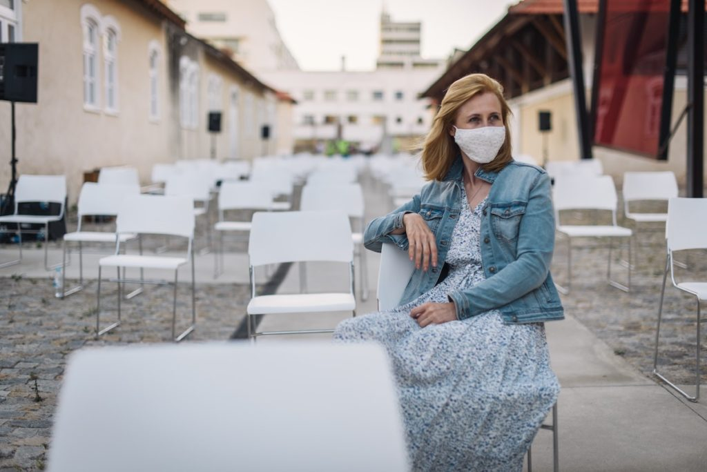 tips to mitigate corona exposure woman sat alone in a mask outdoors