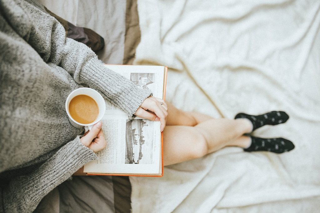 doing one thing for yourself every day woman rwading book with cup of tea