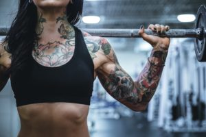 benefits of strength training torso shot of a muscular body lifting a weight