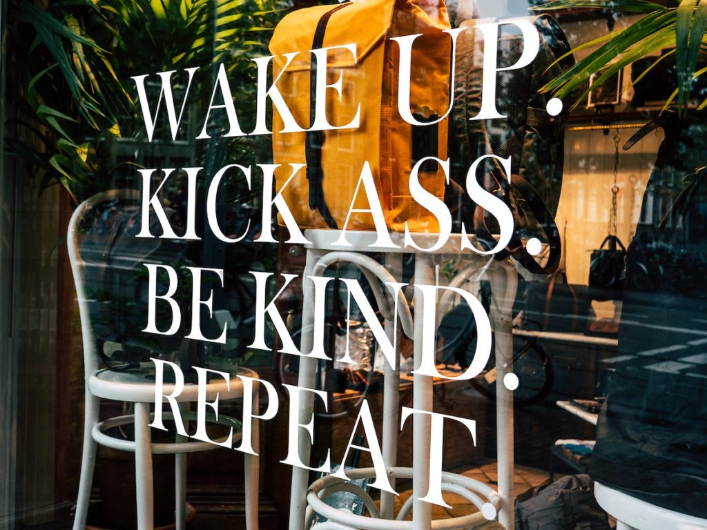 consistency not intensity approach to weelbeing, shop sign saying wake up kick ass be kind repeat