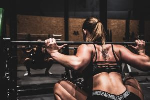 Fitness - Get More From Doing Less. Woman squatting with heavy weights