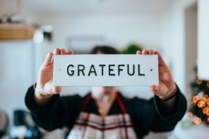 Person holding a grateful sign. Five things you are happy and grateful for