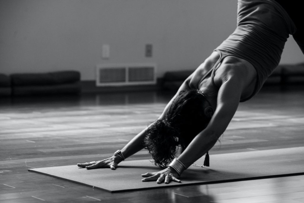 black and white photo of woman in downward dog yoga pose Yoga and mobility preventative health strategy