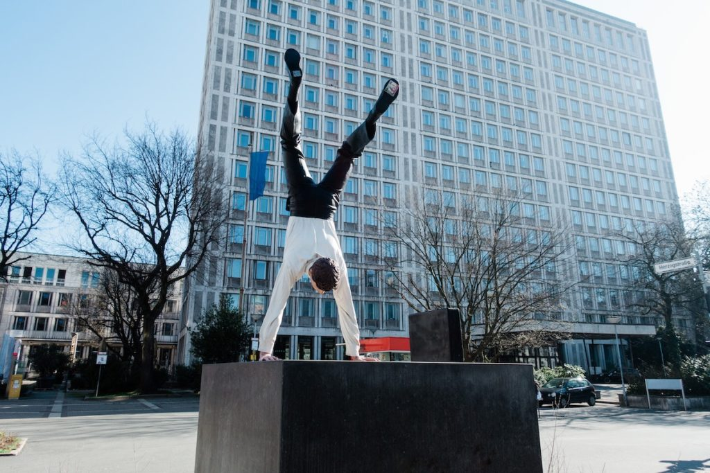 Business Athlete - man in short and suit doing a handstand