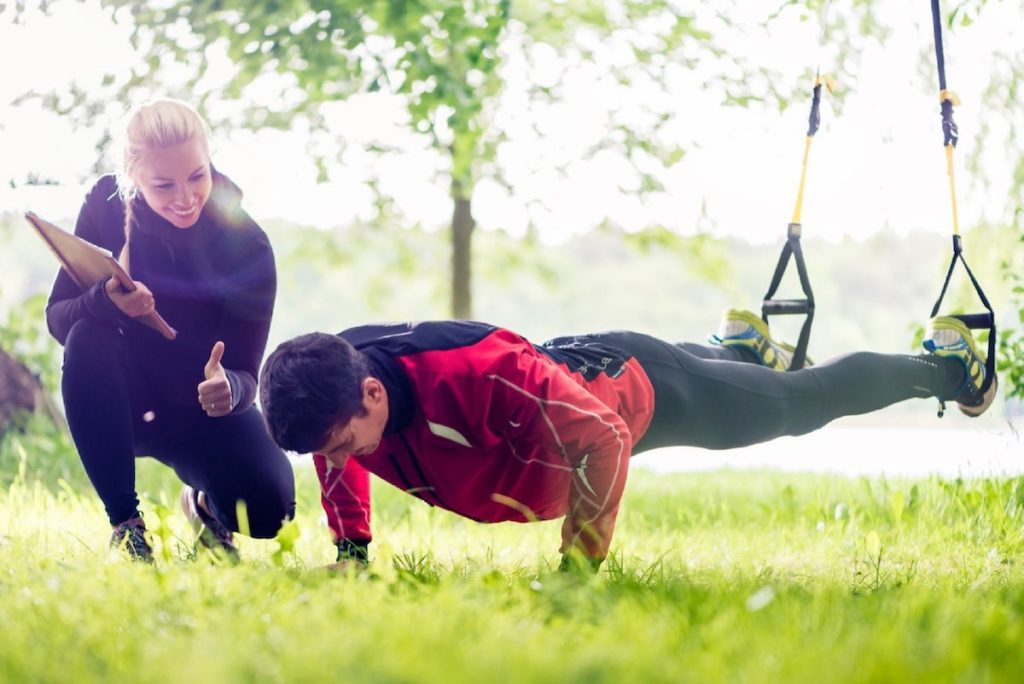 personal trainer motivating trainee doing press ups.