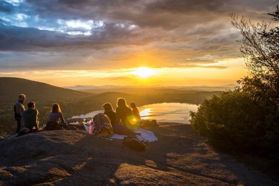 Future Retrospection people sat on a hilltop at sunset