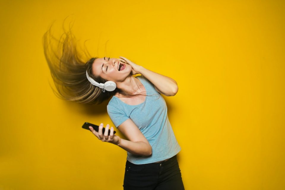Gratitude as part of a preventative health strategy - woman smiling and flicking hair around happily listening to music on headphones