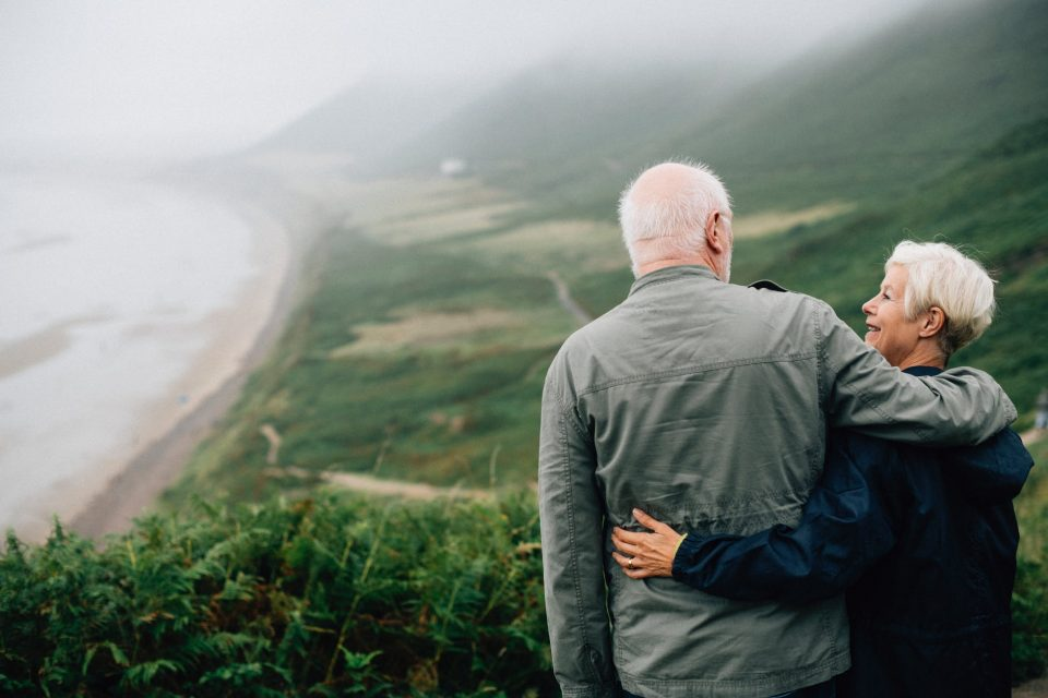 Older man and woman standing on top of a hill looking at each other