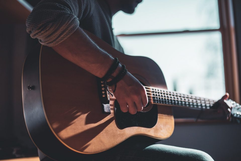 how are hobbies good for wellbeing man playing guitar