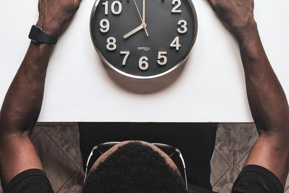 A man sitting at a table looking at a clock sat on the table in front of him