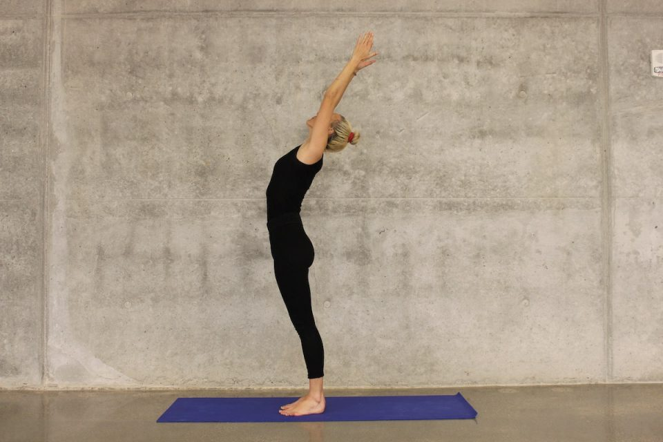 Yoga for anxiety woman stood on a yoga mat with hand up in the air