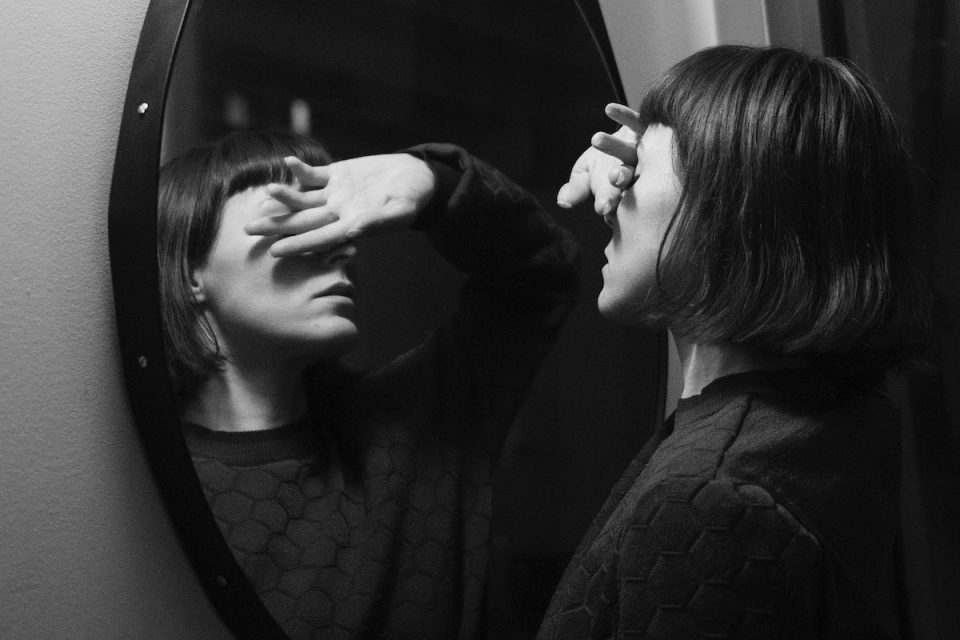are our mirrors ruining our lives blaxck and white photo of woman looking sad in the mirror