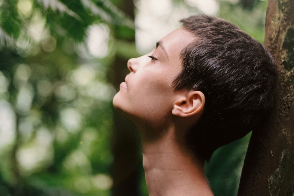 woman in forest doing breathwork
