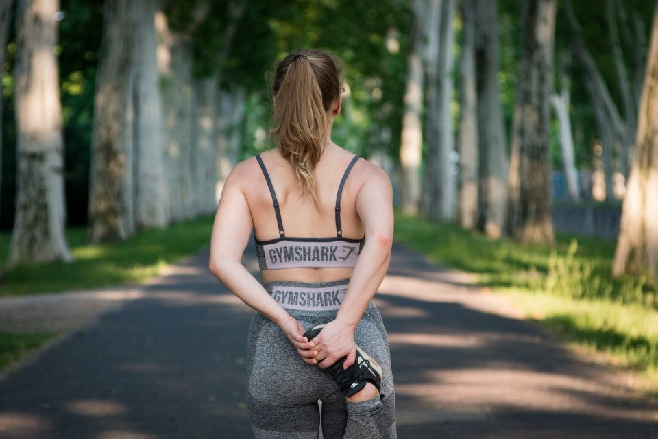 A woman looking at the road ahead in running clothes, stretching her calf muscle