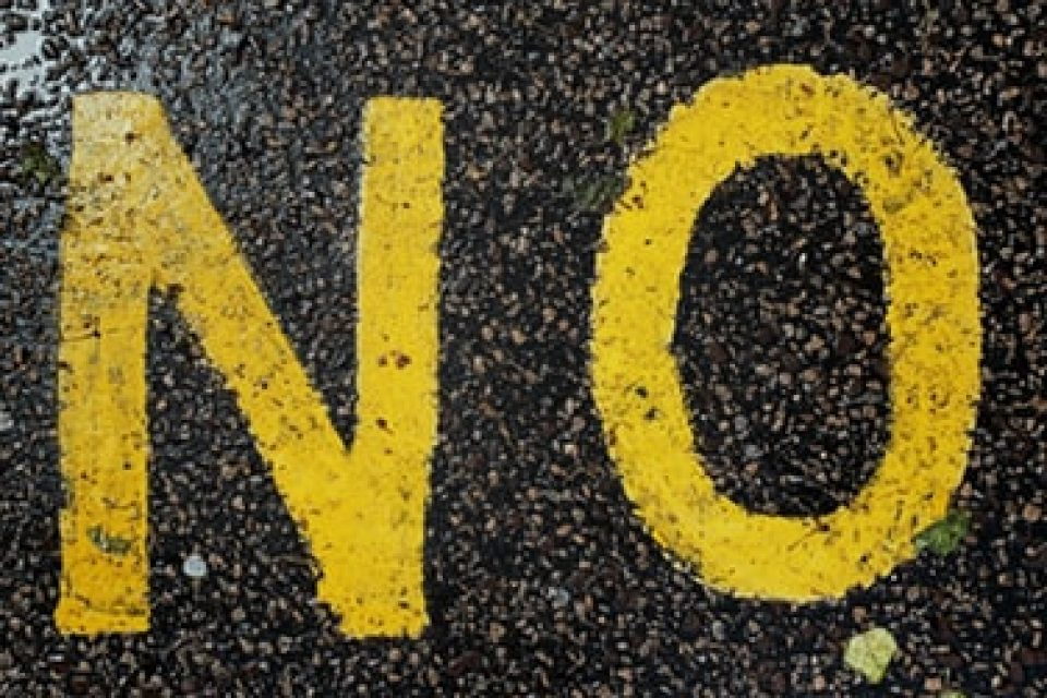 The word no on the pavement with a pair of feet stood in front