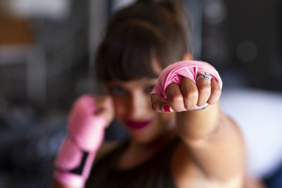 A woman punching out one hand in front of her face