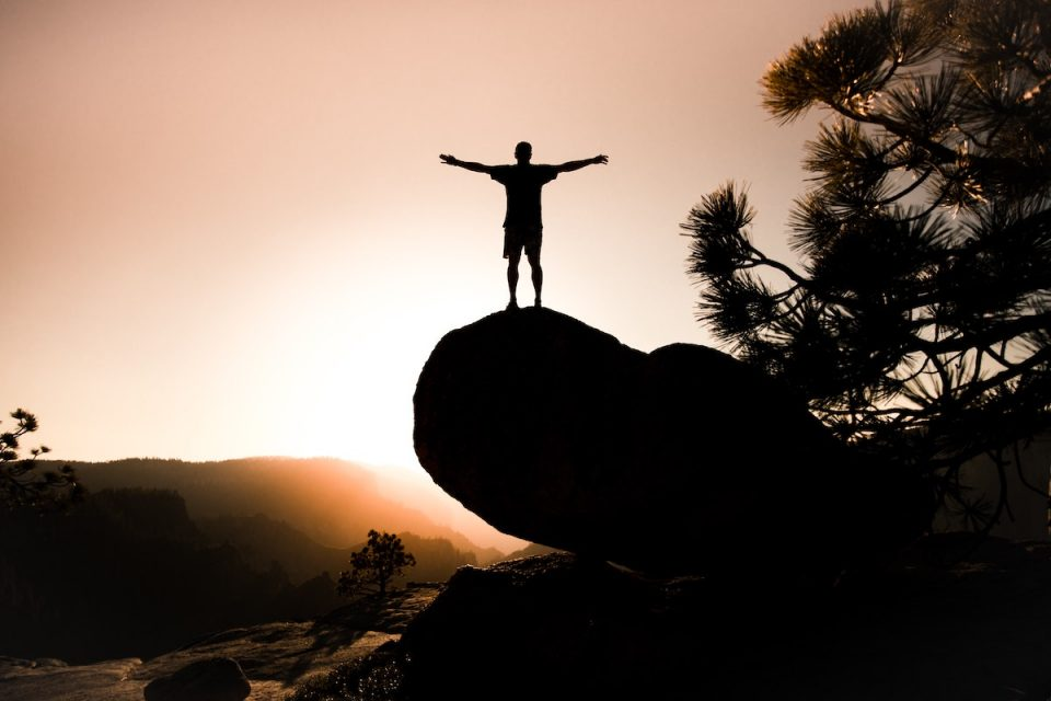 person stood doing the power pose stretching arms wide open at sunset on a rock