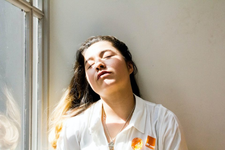Woman waking tired sat with eyes closed