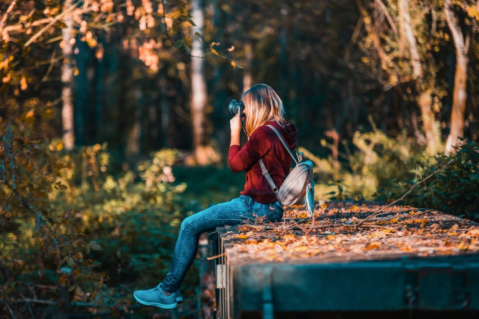 A woman sitting in the woods taking a picture with her camera on an autumn day