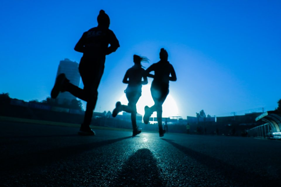 three people running as the sun is going down. what's the best time of day to exercise